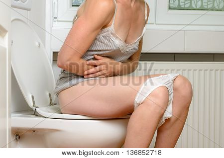 Woman With A Stomach Ache Sitting On A Toilet