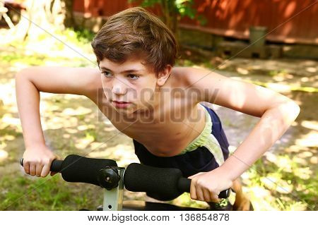 preteen handsome boy make push up on portable trainer in the open air garden yard close up photo