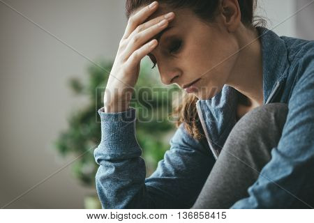 Sad depressed woman at home sitting on the couch looking down and touching her forehead loneliness and pain concept poster