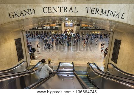 New York, USA - June 19, 2016: Bustling grand central terminal in New York City with sign and view from escalator