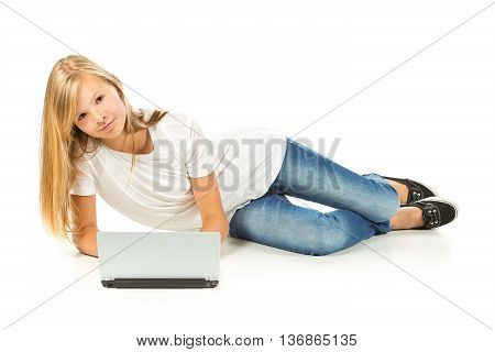 Young girl lying on the floor using laptop over white background
