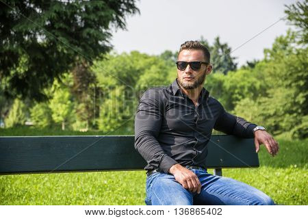 Handsome Muscular Hunk Man Outdoor in City Park, During Daytime, Wearing Black Shirt and Sunglasses