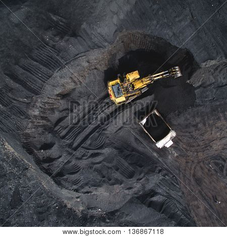 Top view of an excavator loading the truck with coal