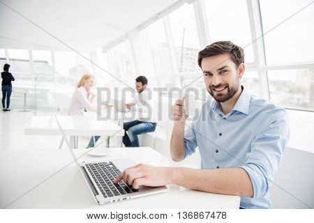 I dream big. Smiling young businessman enjoying his coffee break and working at laptop with colleagues working in background