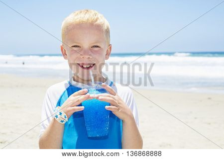 Young boy drinking a blue ice drink at the beach during summer vacation