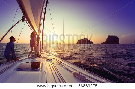 Young lady and man working with sail and rope on the sailing boat
