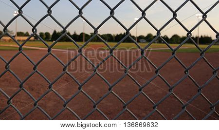 A wide angle shot of a baseball field shot through a chain-link fence at dusk.