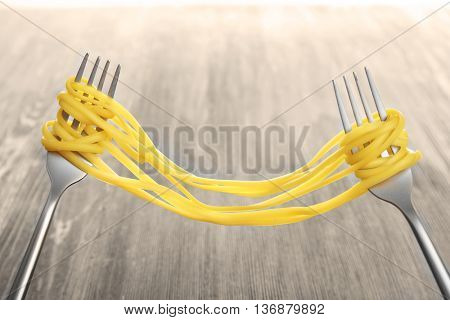 Forks with cooked pasta on wooden background