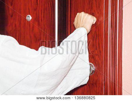 man's hand knocking on the door closeup