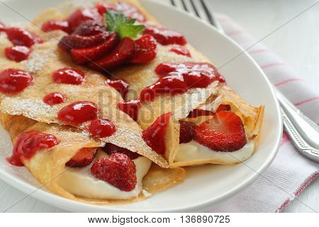 Thin crepes with cheese filling and strawberry sauce