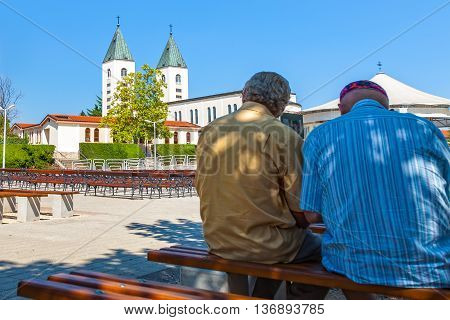 MEDJUGORJE, BOSNIA AND HERZEGOVINA - JULY 20, 2014: Two unidentified pilgrims praying in front of the Saint James church of Medjugorje in Bosnia Herzegovina. Medjugorje since 1981, it has become a popular site of religious pilgrimage due to reports of app