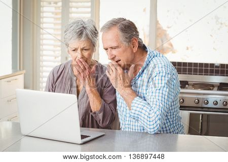 Shocked senior couple looking at laptop while sitting in kitchen