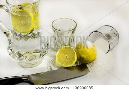 Still life a lemon with sugar and lemon water in the countess on a white background