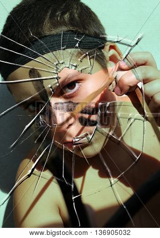 Boy with a slingshot on a background of broken glass