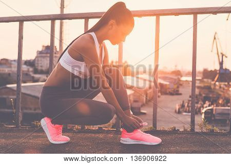 Tying her shoelaces. Beautiful young woman in sports clothing tying her shoelaces while standing on the bridge with evening sunlight and urban view in the background