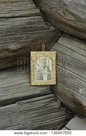 Saint Nicholas icon on grey wood blockhouse wall corner close up