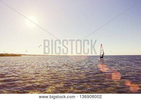 Windsurfing man sails to meet the sun. Sea of people who swim in the windsurfing and kitesurfing. Windsurfing and kite surfing on the sea in summer
