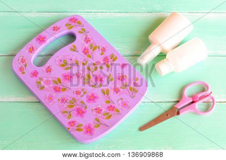Decoupage cutting board kitchen wall decoration. Idea for painting and decoupage on a chopping board. Handmade kitchen decor. Glue, paint, scissors. Tools and materials for for creative work