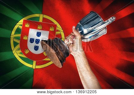 Happy rugby player holding trophy against digitally generated portugese national flag