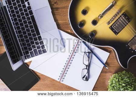 Top view of wooden desktop with blank tablet spiral notepad glasses laptop electric guitar decorative plant and pencil