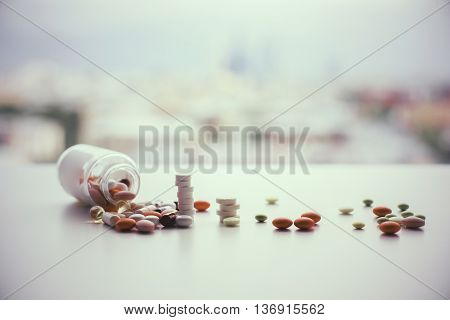Different pills falling out of prescription bottle on blurry city background