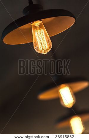 Retro Tungsten Lamps Glowing Over Dark Ceiling