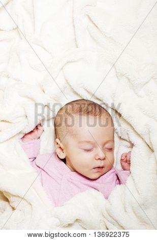 Little cute newborn baby sleeping on its back on a soft blanket. Healthy infant sleep.