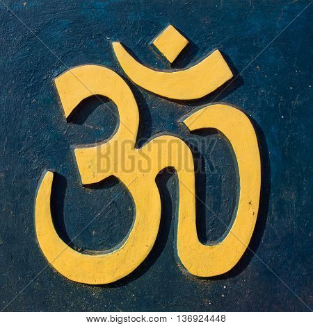 Yellow Om/Aum symbol on dark blue wall
