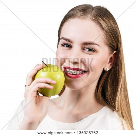 Beautiful young woman with brackets on teeth eating apple isolated on white
