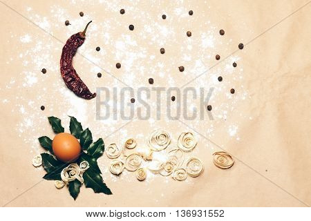Natural background with egg on laurel leaves red chili pepper allspice excelsior on pack paper decorated with white flour copyspace