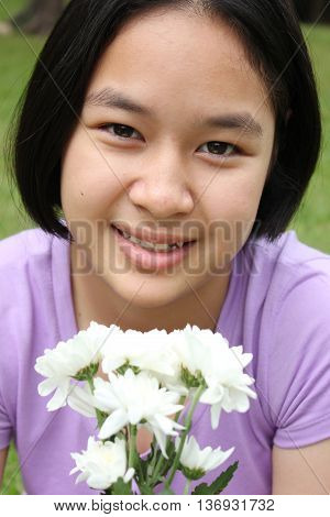 Portrait of cute asian girl holding the flowers, spring time.