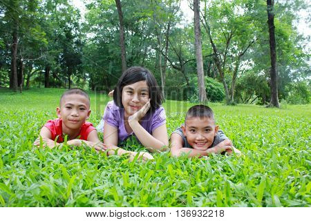 Three asian kids having a good time in the park, spring time.