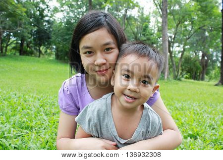 Young girl and little boy having good time in the park, spring time.