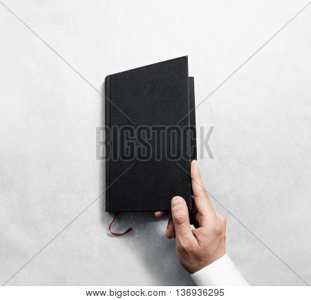 Hand opening blank black book cover mockup template. Clear booklet front surface design mock up. Arm holding opened textbook diary. Reading grey notebook copy. Closed catalogue presentation display.