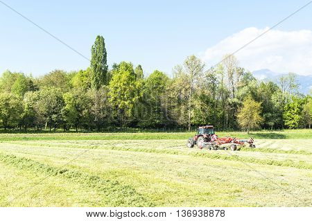 Rotary hay rake in action behind a tractor raking dried grass for baling for hay and winter feed for the livestock on the farm.