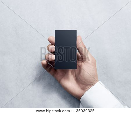 Hand holding blank vertical black business card design mockup. Clear calling card mock up template hold arm. Visit pasteboard paper surface display front. Small dark offset card holder presentation