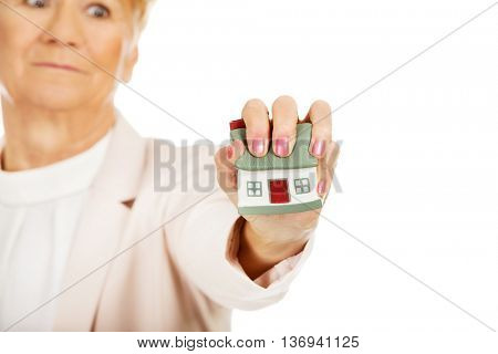Elderly angry business woman crushed house model