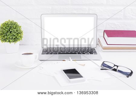 Closeup of blank white laptop on light desktop with smartphone paper coffee cup glasses decorative plant and books on brick wall background. Mock up