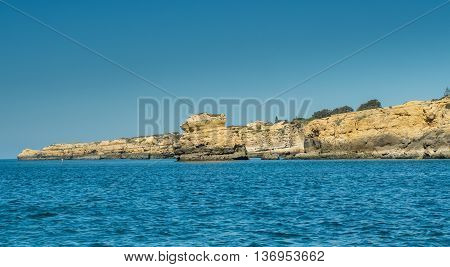 A view of cliff on the Algarve coast from a boat sailing on the sea in Portugal 2016