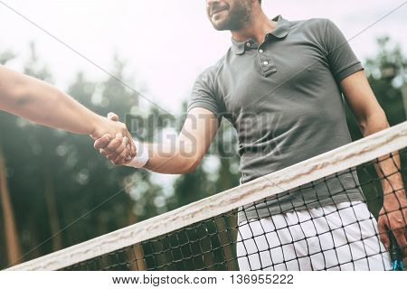Thank you for the game! Low angle view conceptual image of two man in sports clothing shaking hands while standing near the tennis net on court