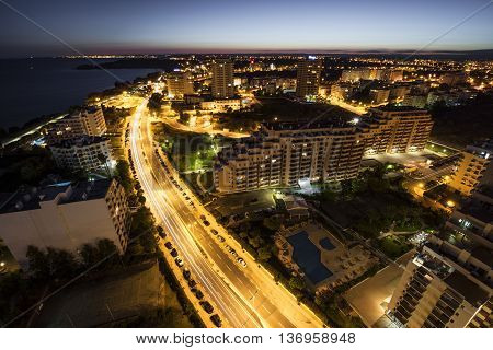 City at the bank of the ocean with buildings and hotels during sunset. View from above. Portimao Algarve Portugal.