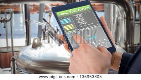 Businessman using digital tablet over white background against open door of large vat