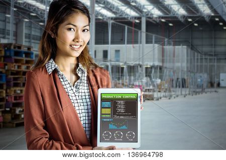 Smiling businesswoman showing a tablet against image of a warehouse