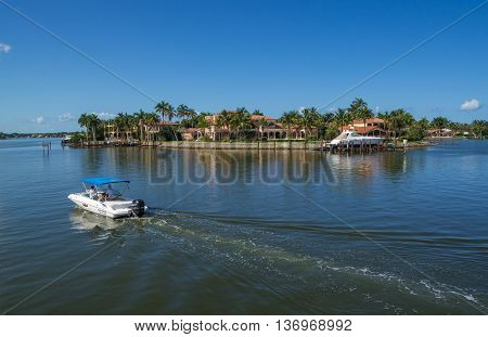 NAPLES, FLORIDA, USA - May 8 2013: Rental Boat Cruising Past Large Luxury Waterfront Mansion in the Bayside area of Naples. Naples is one of the wealthiest cities in the United States