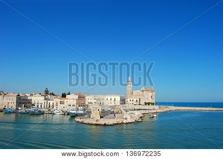 The pier of the port and the famous church of Trani in Apulia - Italy
