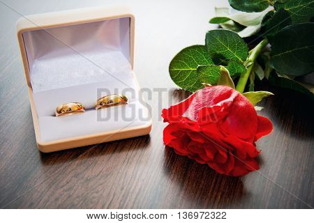 Wedding rings in the case for rings with red rose. Marriage and wedding concept image.