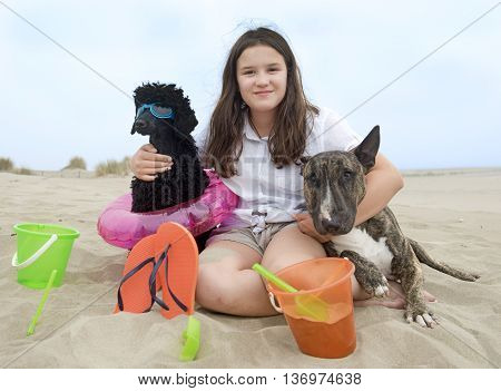 young girl and her two dogs on the beach
