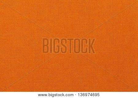 Bright orange background from a textile material. Fabric with natural texture. Cloth backdrop.