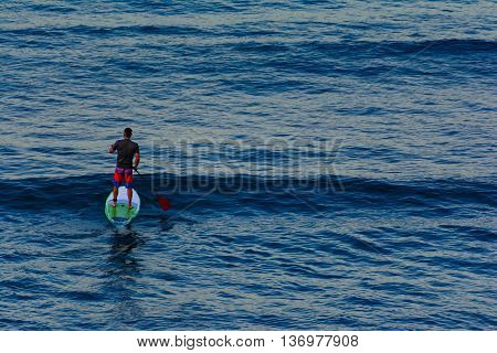 Lone Paddleboarder on the water at dawn. Calm blue water with rolliing waves