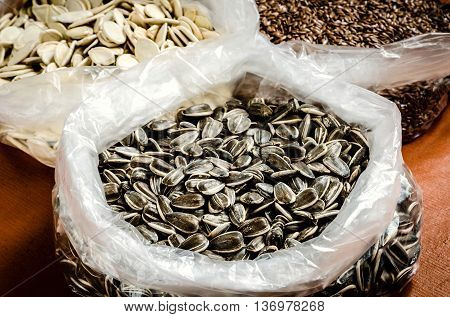 Sunflower with pumpkin seeds and linseeds in the background. Healthy food in folic bags.